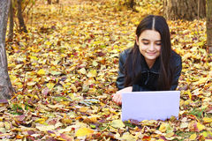 Teenager laying on leaves with laptop Stock Images