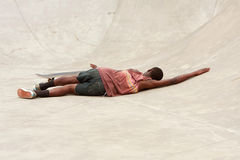 Teenager Lays On Concrete After Wiping Out During Skateboard Run Royalty Free Stock Photography