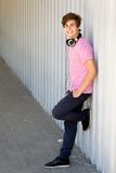 Teenager leaning against wall Stock Photo