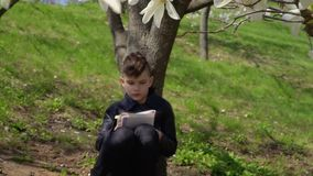 Cute boy in leather jacket writes poem sitting under the tree in park. Teenager in leather jacket sits under blooming tree in park and writes a poem in his stock video