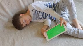 Teenager lies and plays on the tablet. With the screen Hromakey stock video