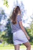 Teenager Lifestyle Concepts and Ideas.Back of Blond Caucasian Teenager Girl Outdoors. Stock Photo