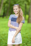 Teenager Lifestyle Ideas. Happy Smiling Teenage Girl in Striped T-Shirt Posing Outdoors in Forest Royalty Free Stock Photos