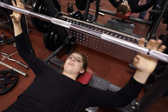 Teenager lifting barbell with weight Stock Photography