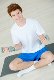 Teenager lifting weights whilst sat on floor Royalty Free Stock Photography