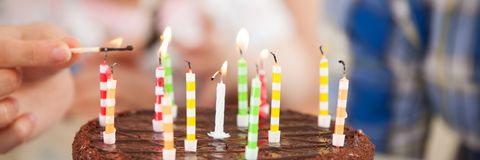 Teenager lights the candles on a birthday cake stock image