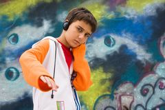 Teenager listening music against a graffiti wall Royalty Free Stock Image