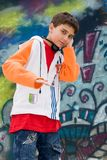 Teenager listening music against a graffiti wall Stock Image