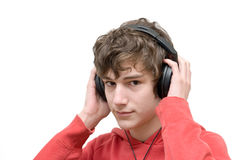 Teenager listening music with headphones. Isolated on pure white Stock Images