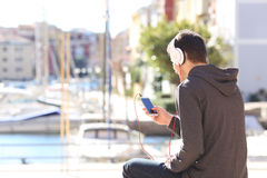 Teenager listening music from smart phone Stock Images