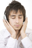 Teenager listening to music. With large headphones stock image