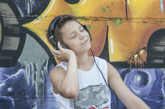 Teenager listening to music on headphones Stock Images