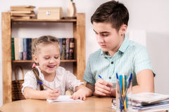 Teenager and a little girl learning Stock Photography