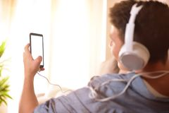 Teenager looking at a mobile and listening to music behind Royalty Free Stock Photography