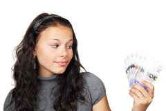 Teenager looking at money. Young woman looking curiously at money Stock Image