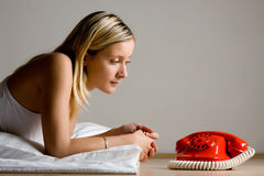 Teenager looking at red phone Royalty Free Stock Images
