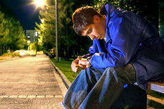 Teenager looking on the watch. Teenager sitting in the night park alley and looking on the watch Royalty Free Stock Photos