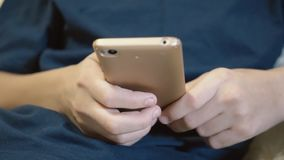 A teenager looks through the news on his smartphone. Hands hold the phone close-up. stock video