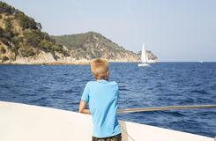 Teenager looks at the sea from the deck of a boat Stock Photos