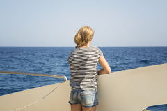 Teenager looks at the sea from the deck of a boat Royalty Free Stock Photography