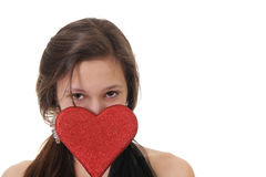 Teenager in love. Teenager girl holding a red heart in front on her eyes Royalty Free Stock Photos