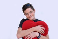 Teenager in love. Cute teenage  boy hugging a heart shaped pillow Stock Images