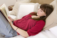Teenager lying on bed reading a book Stock Photography