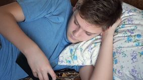 A teenager is lying down and browsing the tablet stock video