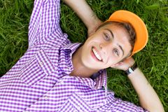 Teenager lying down on grass. Young man lying down on grass Royalty Free Stock Photos