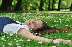 Teenager lying in grass Stock Images