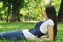 Teenager lying in grass Royalty Free Stock Image