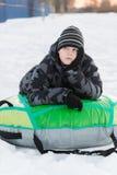 Teenager lying on green tubing Royalty Free Stock Image