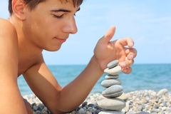 Teenager lying on seacoast, creates pyramid Royalty Free Stock Images
