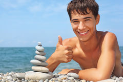 Teenager lying on seacoast, shows ok gesture Royalty Free Stock Photo