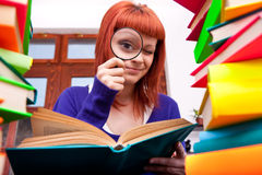 Teenager with magnifier and books Stock Photography