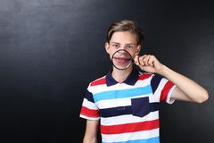 Teenager with magnifying glass. Cute teenager with magnifying glass on blackboard background Royalty Free Stock Photography