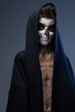 Teenager with make-up of the skull in black cape Stock Photo
