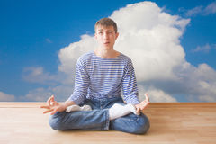 Teenager making funny face while sitting in lotus pose Royalty Free Stock Photos