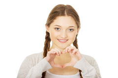 Teenager making heart shape with hands. Smiling teen woman making heart shape with her hands Royalty Free Stock Photography