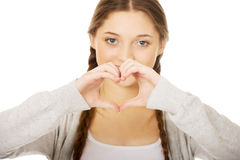 Teenager making heart shape with hands. Stock Photos