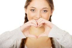 Teenager making heart shape with hands. Smiling teen woman making heart shape with her hands Stock Images