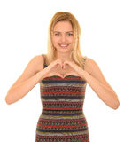 Teenager making heart. Teenage girl in colorful dress making a heart shape with hands while smiling Stock Photo