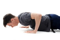 Teenager making push ups in jeans and t-shirt isolated on white Royalty Free Stock Photo