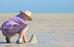 Teenager making sandcastles. On the beach Stock Photos