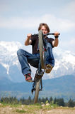 Teenager making Tricks on Bike. Teenager making tricks on a bicycle with mountains in the background Royalty Free Stock Image