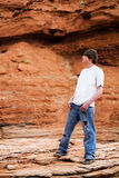Teenager male in mountains. Teenager standing on a rock in the mountains of wyoming. Muddy shoes, holes in jeans, hands in pocket royalty free stock photo