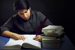 Teenager male writing by books with feather Stock Image