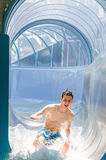 Teenager man happy going down on a water slide Royalty Free Stock Photos