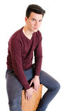 Teenager man musician in sweater sit and play the cajon isolated Stock Photography