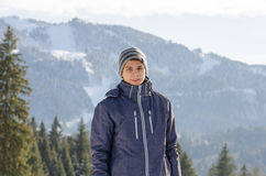 Teenager man smiling in winter jacket at mountains with ski slop Stock Photography
